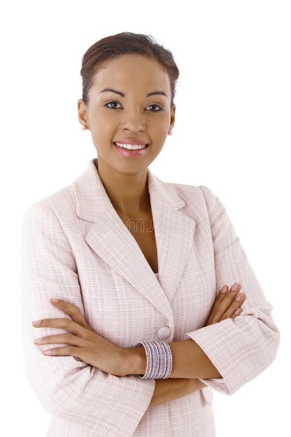 Businesswoman portrait. Portrait of young ethnic businesswoman smiling at camera confidently with arms crossed stock photography