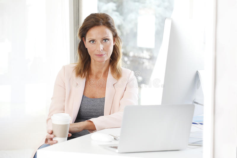 Businesswoman portrait. Portrait of confident businesswoman has a coffee break at office while sitting at desk in front of laptop stock images