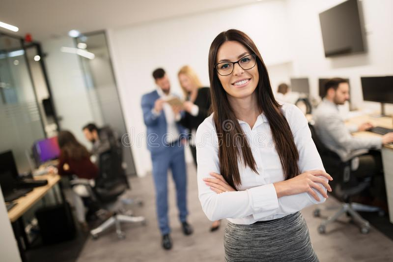 Businesswoman posing while other businesspeople talking in background royalty free stock photography