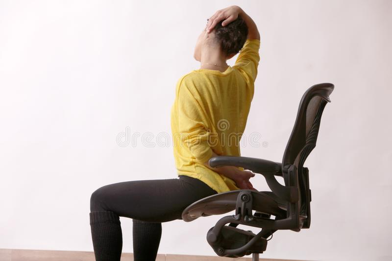 Businesswoman practices exercises at workplace royalty free stock photography