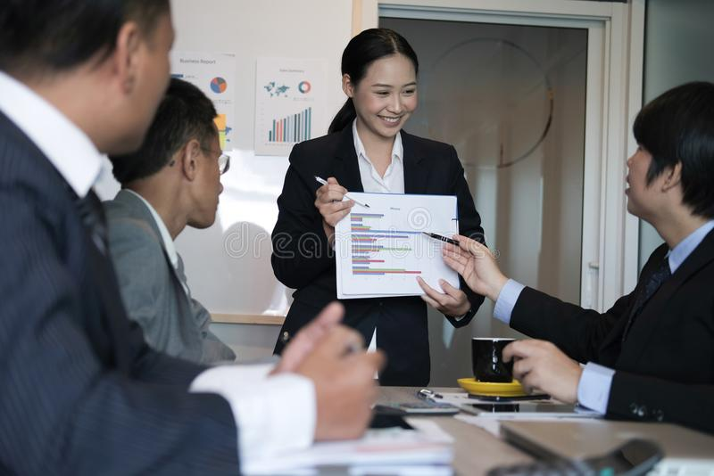 Businesswoman present financial plan report to co worker team. w. Omen leader discuss sales data with investor colleagues. finance investment business meeting at royalty free stock image