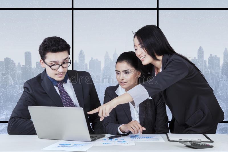 Businesswoman presenting document on the laptop. Portrait of female entrepreneur showing business document on the laptop to her partners stock photo