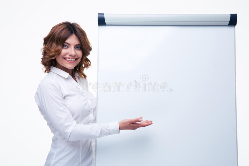 Businesswoman presenting strategy on flipchart. Smiling businesswoman presenting strategy on blank flipchart isolated on a white background. Looking at camera royalty free stock image