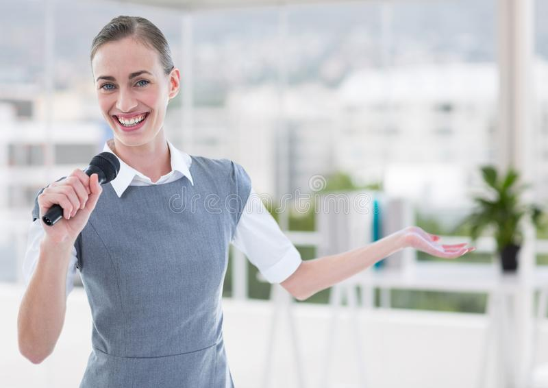 Businesswoman public speaking on microphone in office stock image