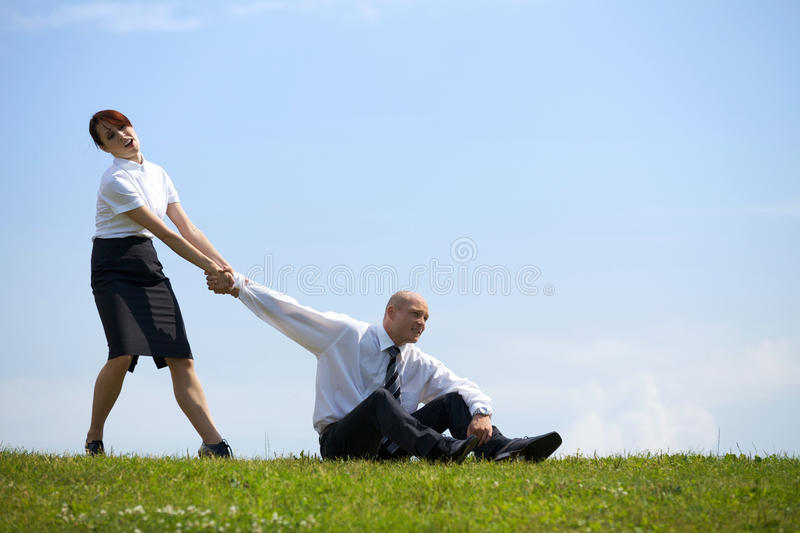 Businesswoman pulling businessman's hand in park stock photography