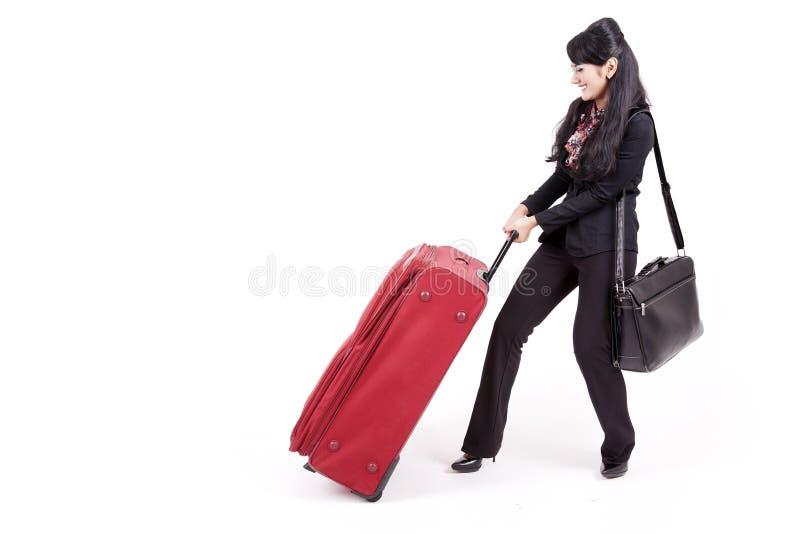Businesswoman pulling heavy suitcase
