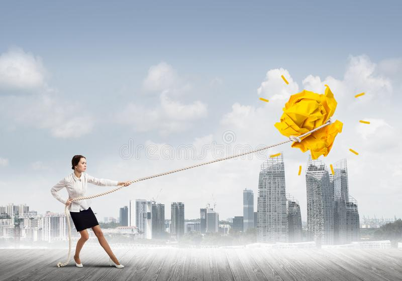 Businesswoman pulling paper ball with rope and making it raise up royalty free stock images