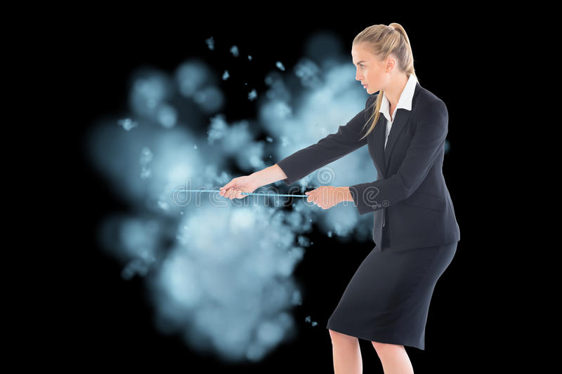 Businesswoman pulling a rope. Composite image of blonde businesswoman pulling a rope stock photography