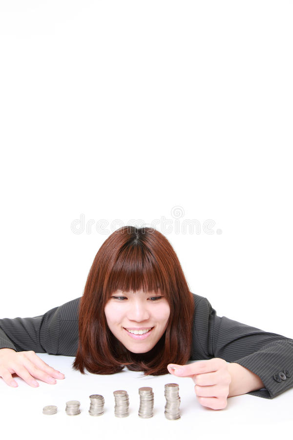 Businesswoman put coins to stack of coins. Studio shot of young Japanese businesswoman on white background stock photography