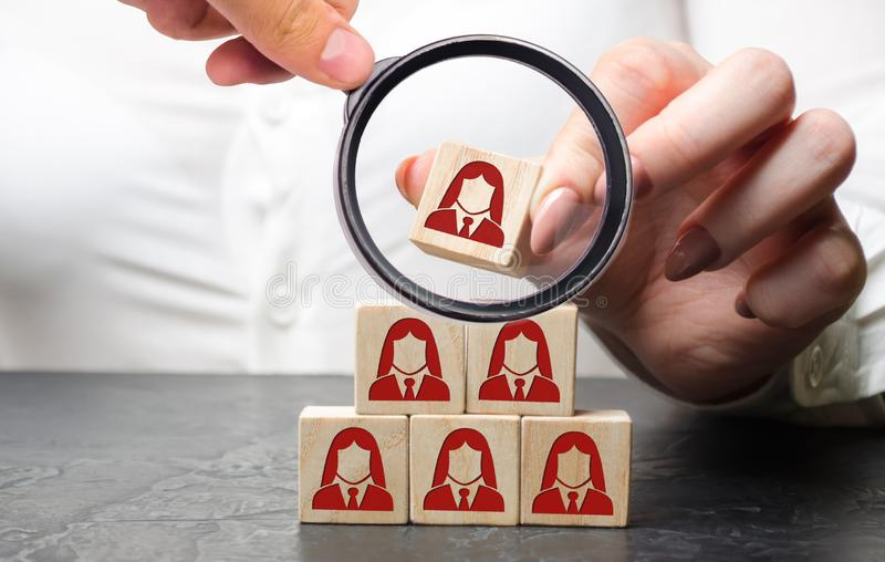 Businesswoman puts wooden blocks with the image of female employees. The concept of management in a team. Human resources. Women`. S team. Hiring workers royalty free stock photos