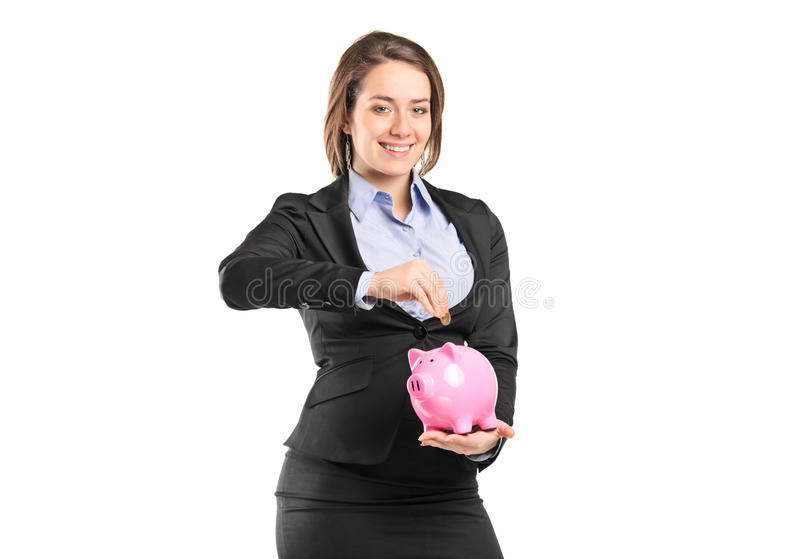 A businesswoman putting a coin into a piggy bank