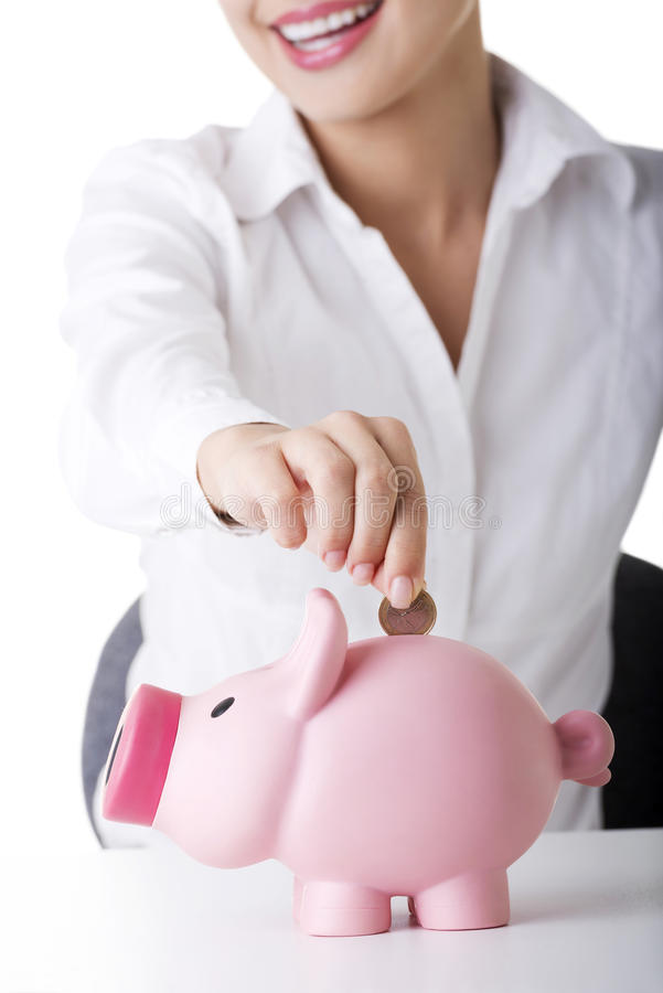 Businesswoman putting a coin into a piggy bank royalty free stock photos
