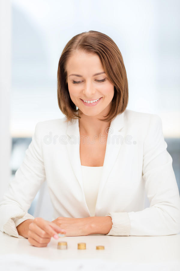 Businesswoman Putting Euro Coins Into Columns Stock Photo