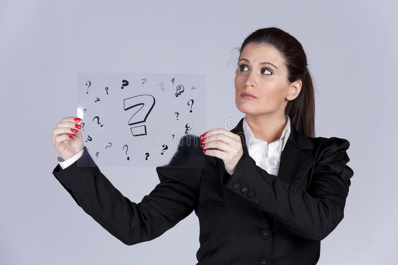 Businesswoman questions. Businesswoman holding a acetate with lots of question marks stock photos