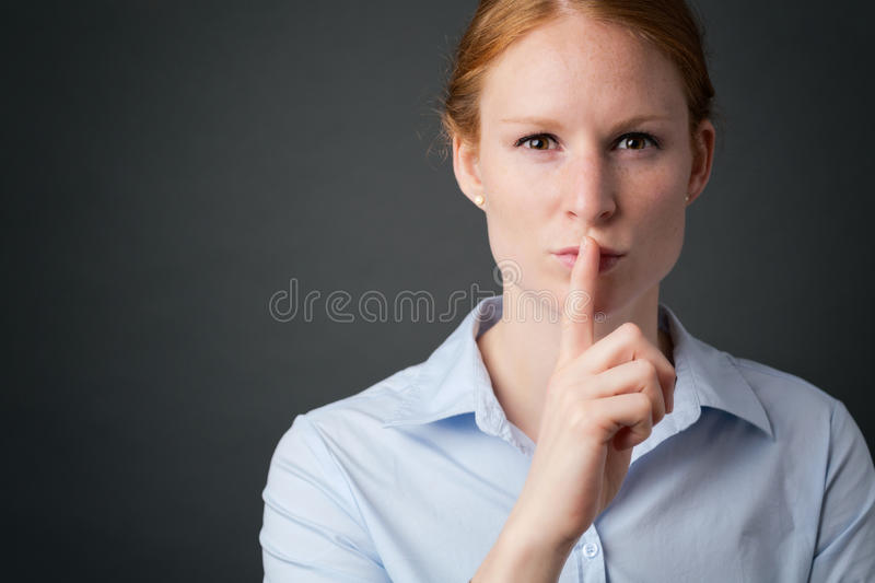 Businesswoman - Quiet or Keep a Secret. Young businesswoman gestures for silence or keeping a secret with one finger before her lips royalty free stock photos