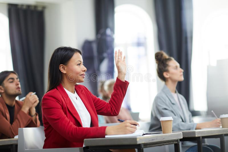 Businesswoman Raising Hand in Seminar. Side view portrait of smiling mixed-race businesswoman raising hand in class during training course on business and royalty free stock photography