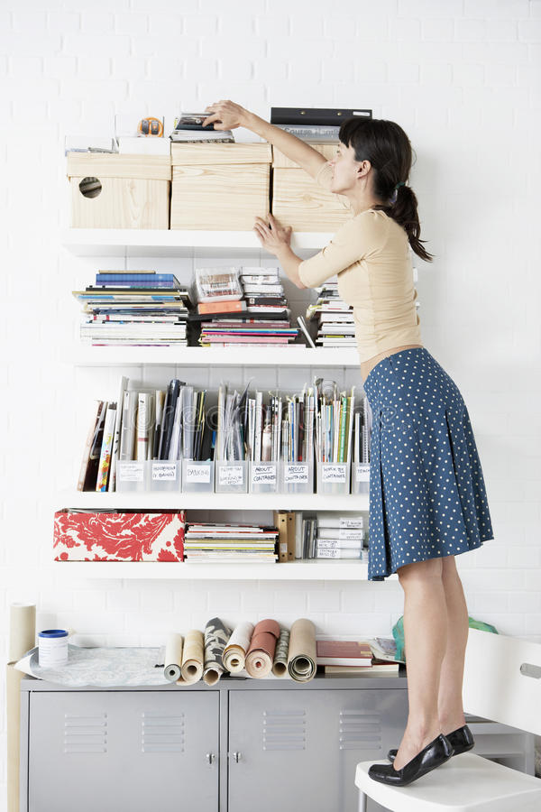 Free Businesswoman Reaching For Shelf In Home Office Royalty Free Stock Photo - 31834315