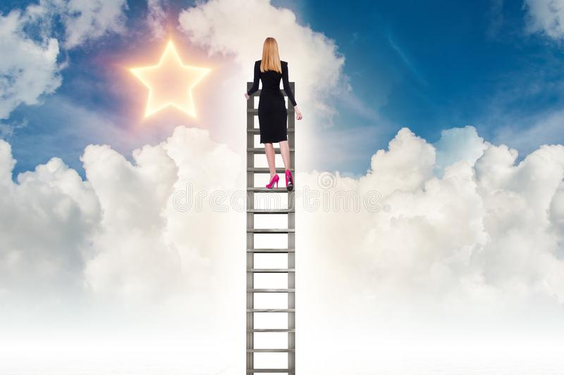 Businesswoman reaching out for stars in success concept stock photography
