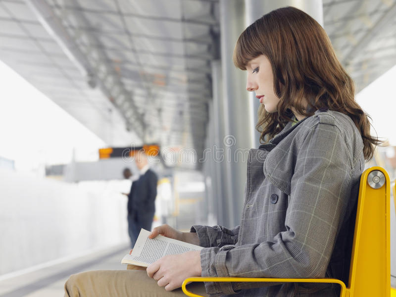 Businesswoman Reading Book At Train Station. Side view of a businesswoman reading a book at train station bench stock photos