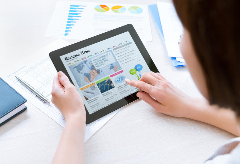 Businesswoman reading latest news. Businesswoman wearing casual shirt sitting at desk and looking latest business news on digital tablet in the office stock image