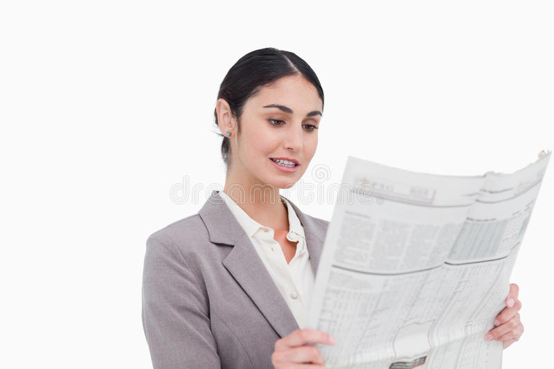 Businesswoman reading news paper. Against a white background royalty free stock photo