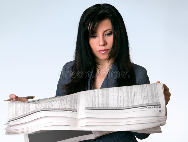 Businesswoman reading newspaper. A businesswoman reading the finance section of a newspaper stock photos