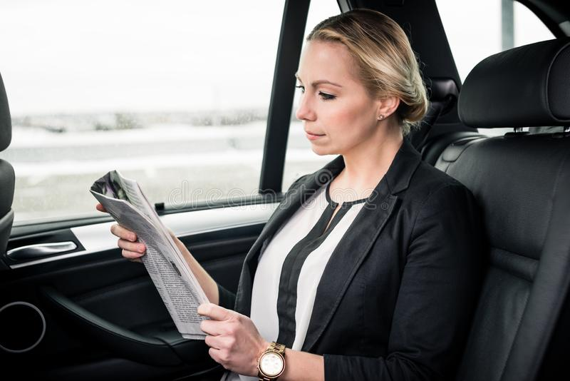 Businesswoman reading newspaper in car stock photo