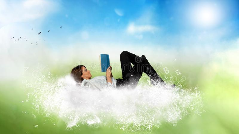Businesswoman reads a book over a cloud made of letters. Concept of relax and imagination. stock image
