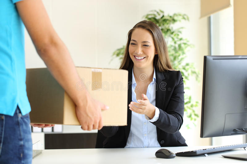Businesswoman receiving a package. Happy businesswoman receiving a package sitting on a desk at office stock image