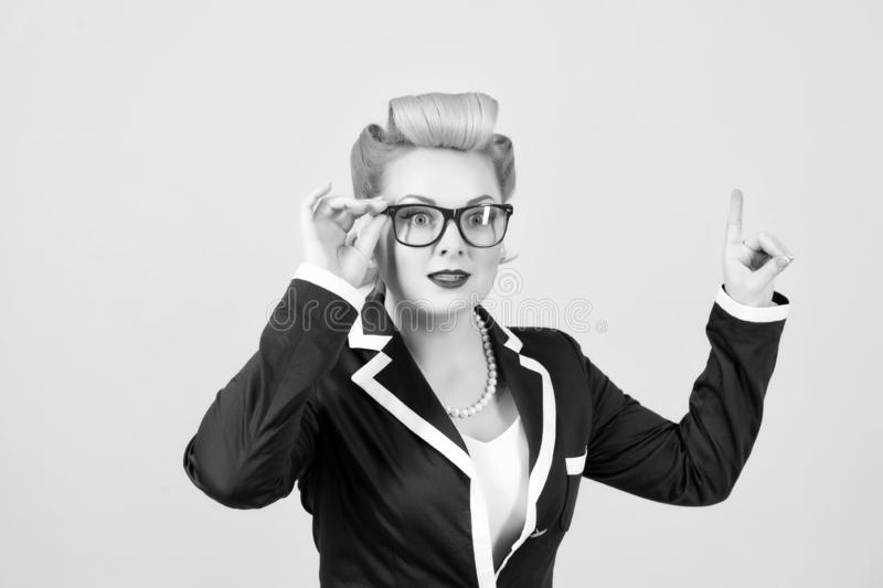 Businesswoman in red glasses points up on grey background. Lady with finger up royalty free stock photos