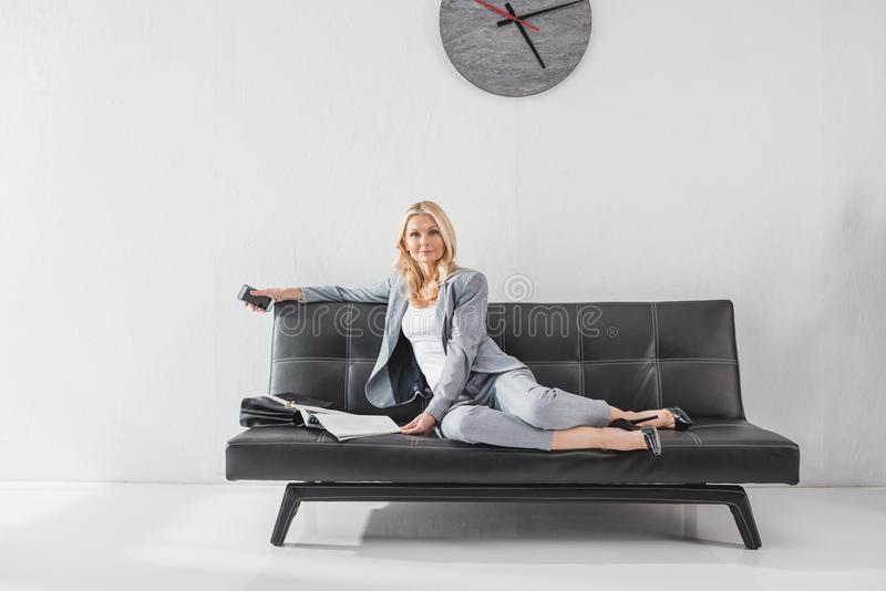 Businesswoman relaxing on couch with magazine. Stylish mature businesswoman relaxing on couch with magazine royalty free stock photo