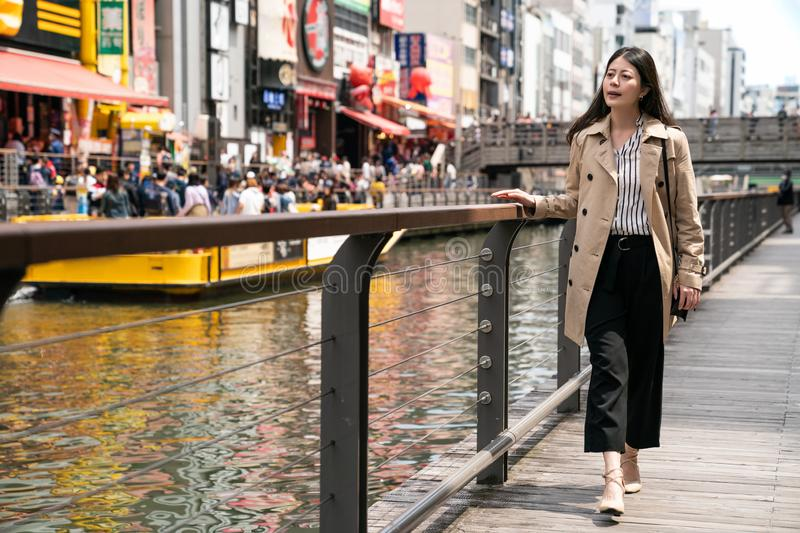 Businesswoman relaxing and walking beside river. Businesswoman relaxing and walking beside the river, she puts her hands on the handrail royalty free stock images