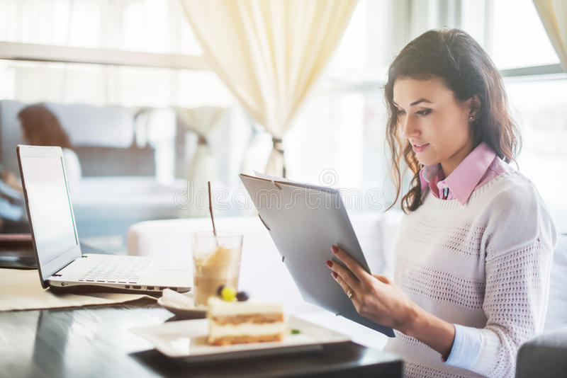 Businesswoman in a restaurant reading contract document. stock photography