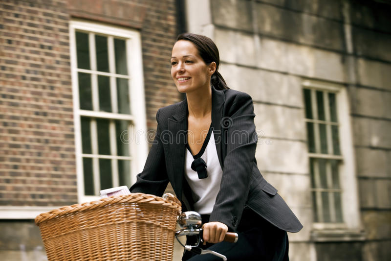 A businesswoman riding a bicycle, smiling stock images