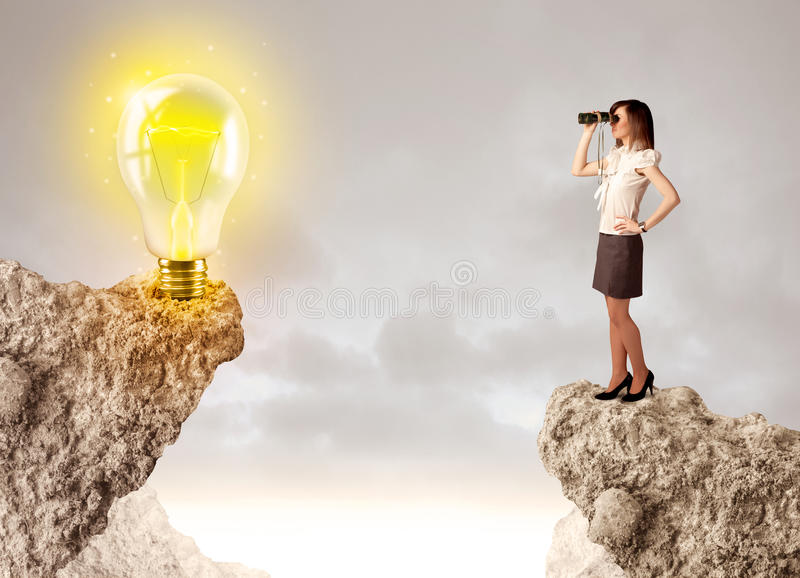 Businesswoman on rock mountain with idea bulb. Businesswoman standing on the edge of rock mountain with an idea bulb on the other side royalty free stock image