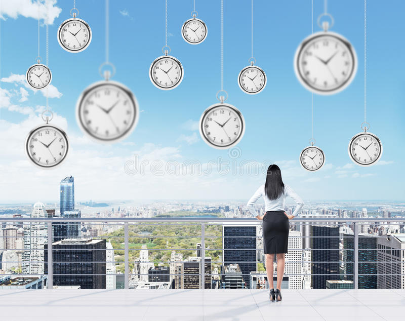 Businesswoman on the roof. Businesswoman standing with hands on hips on the roof of a business centre and looking at New York. Pocket watches hovering from above stock photos