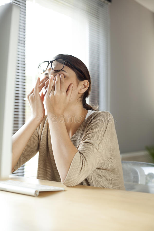 Businesswoman rubbing her tired eyes. Businesswoman rubbing her tired and eyes stock image