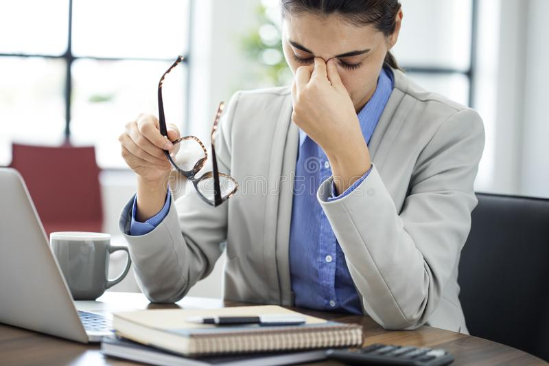 Businesswoman rubbing her tired eyes royalty free stock image