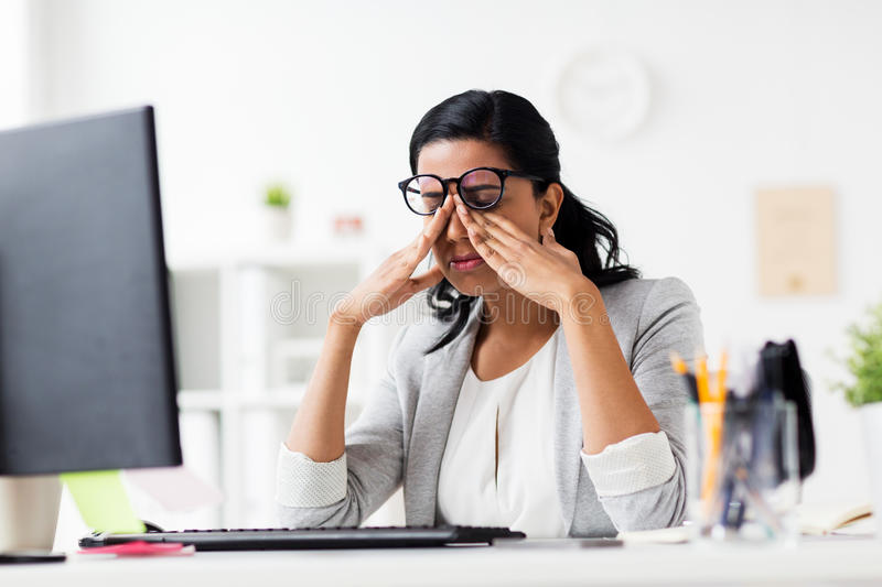 Businesswoman rubbing tired eyes at office. Business, overwork, deadline, vision and people concept - tired businesswoman in glasses working at office and royalty free stock photo