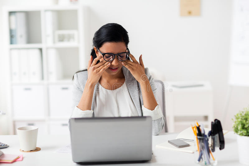 Businesswoman rubbing tired eyes at office. Business, overwork, deadline, vision and people concept - tired businesswoman in glasses working at office and stock photos