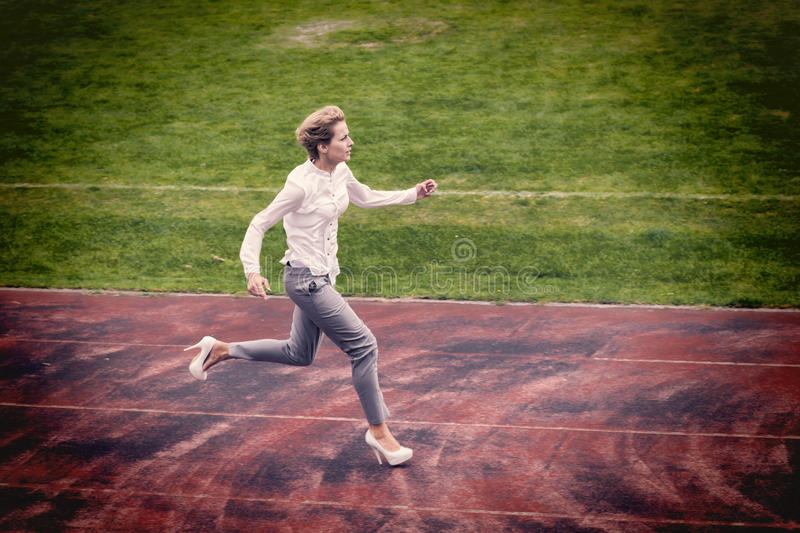 Businesswoman running outdoor on a racecourse. Businesswoman running fast outdoor on a racecourse royalty free stock photo