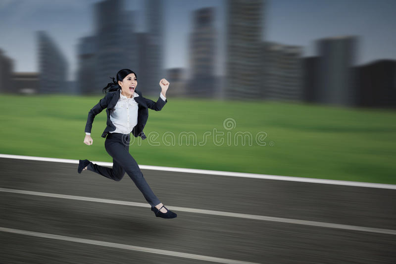 Businesswoman runs on a running track. Young businesswoman is running on a track with cityscape background royalty free stock photography