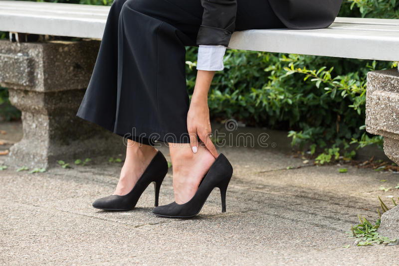 Businesswoman`s Hand Removing High Heels royalty free stock photos