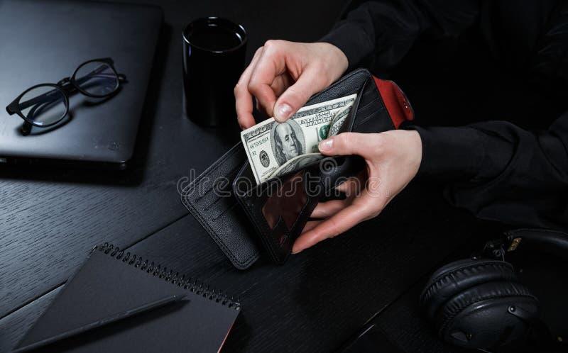 Businesswoman& x27; s-handen i dräkt tar ut dollarpengar från en plånbok Begreppet av finans Närbild arkivbilder