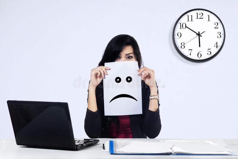 Businesswoman with a sad emoticon stock image