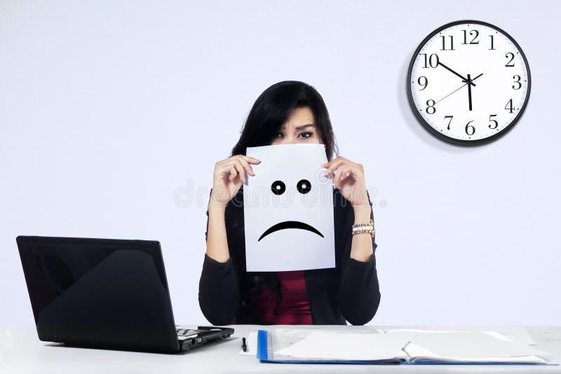 Businesswoman with a sad emoticon. Portrait of unhappy businesswoman showing a sad emoticon stock photos
