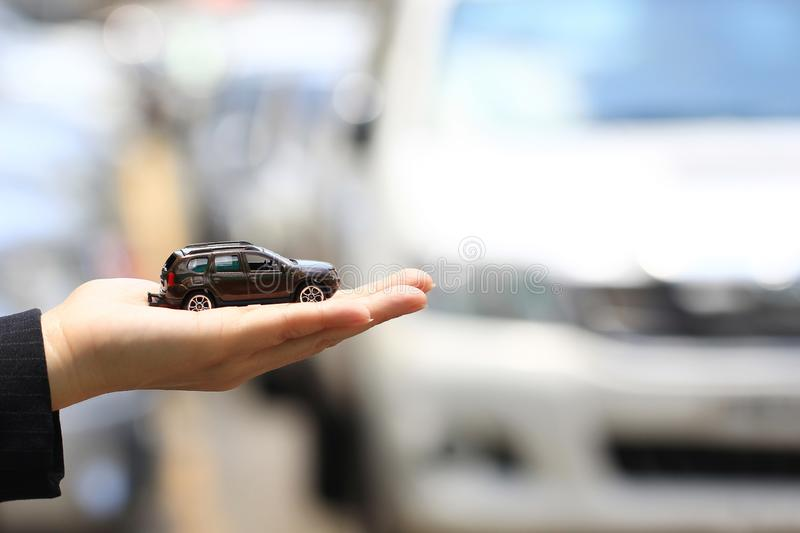 Businesswoman or saleswoman holding miniature car model, auto business, car trading, loans for car concept.  stock image