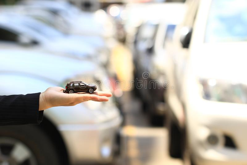 Businesswoman or saleswoman holding miniature car model, auto business, car trading, loans for car concept.  stock photography