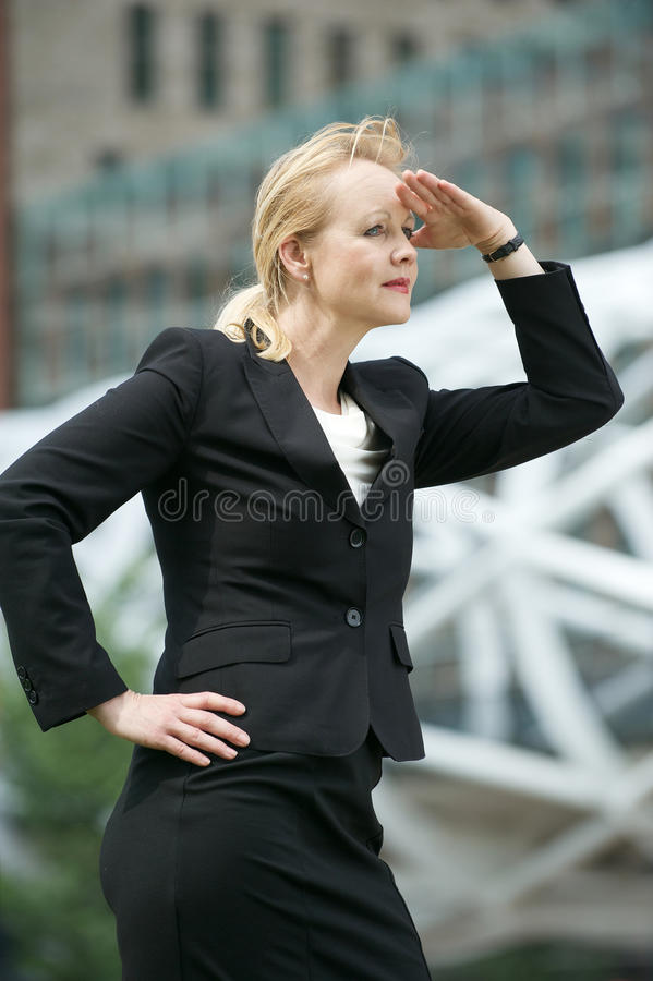 Businesswoman salute with hand to head looking in the city. Portrait of a businesswoman salute with hand to head looking in the city royalty free stock photo