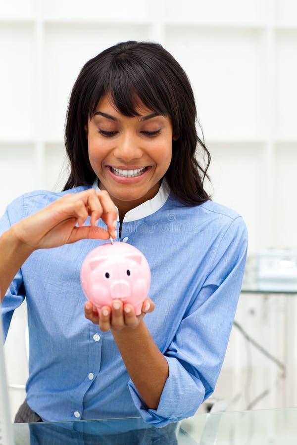 Businesswoman saving money in a piggy-bank stock image